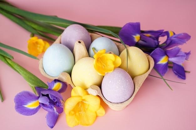 Ovos de páscoa coloridos em uma bandeja e flores em um fundo rosa. vista do topo