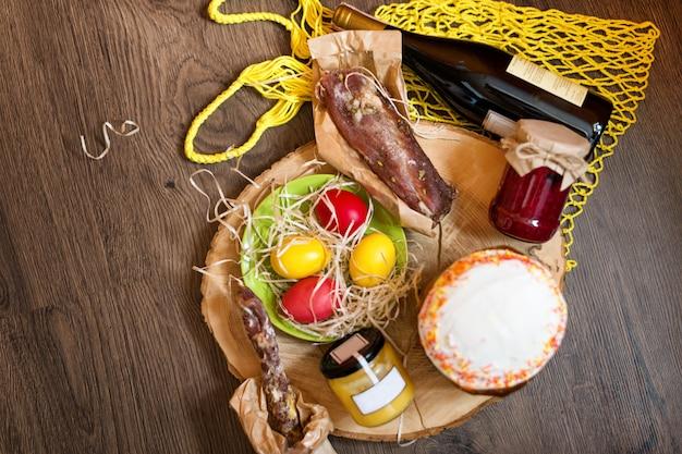 Ovos de páscoa coloridos em uma cesta com bolo, vinho tinto, hamon ou salsicha defumada seca e espasmódica
