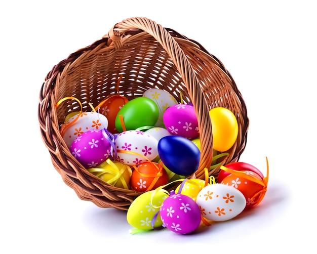 Ovos de páscoa coloridos em uma cesta de madeira, isolada no fundo branco.
