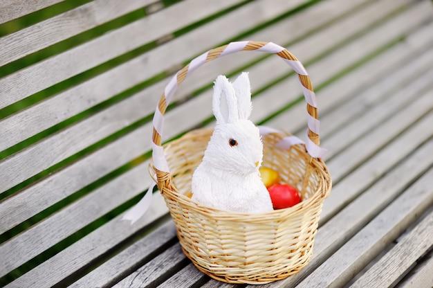 Ovos de páscoa coloridos em uma cesta no banco de madeira com coelho de brinquedo branco bonito