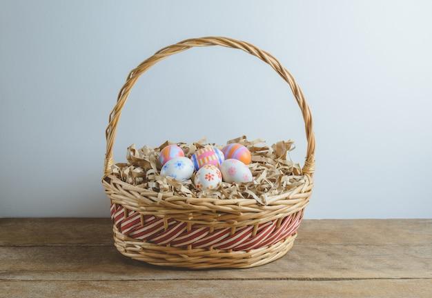 Ovos de páscoa coloridos feitos à mão em papel de palha na cesta