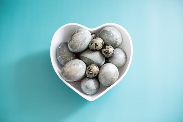 Ovos de páscoa coloridos lindos na tigela de coração em azul