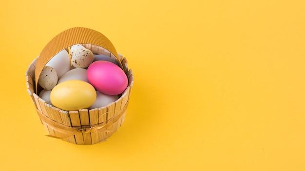 Ovos de páscoa coloridos na cesta de madeira