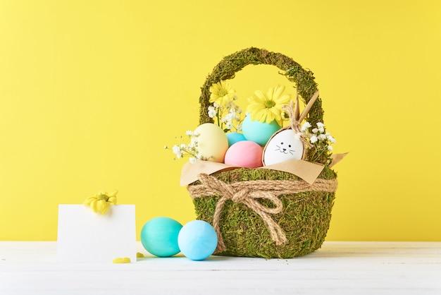 Ovos de páscoa coloridos na cesta decorativa em um fundo amarelo