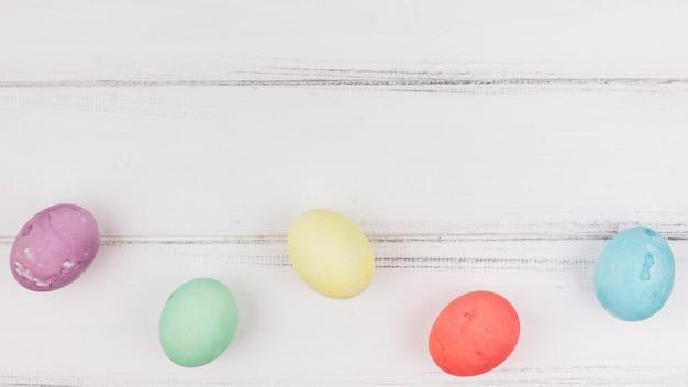 Ovos de páscoa coloridos na mesa de madeira