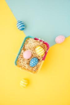 Ovos de páscoa coloridos na pequena cesta na mesa