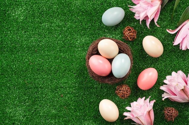 Ovos de páscoa coloridos no ninho com flor de lírio rosa em uma superfície de grama de gramado.