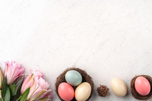 Ovos de páscoa coloridos no ninho com flor de lírio rosa na superfície da mesa de mármore branco brilhante.