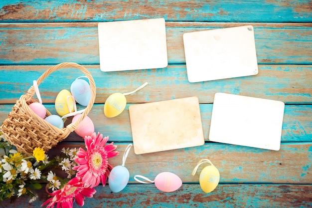 Ovos de páscoa coloridos no ninho com flor e vazio velho álbum de fotos de papel na mesa de madeira