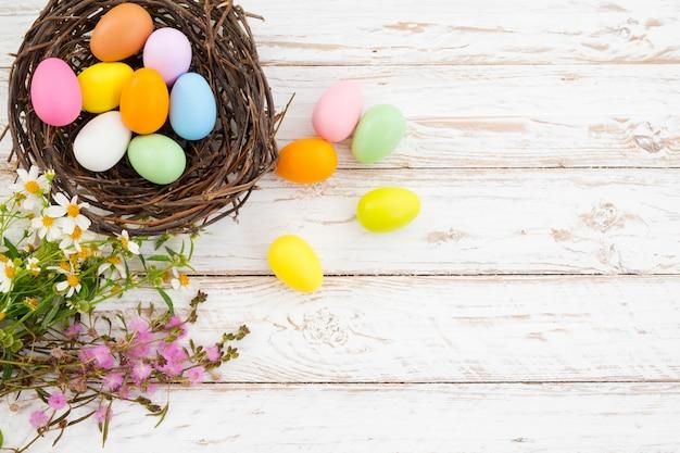 Ovos de páscoa coloridos no ninho com flor em fundo de pranchas de madeira rústica em tinta branca