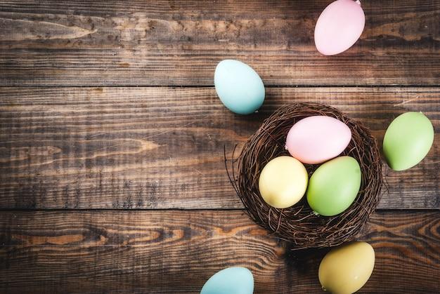 Ovos de páscoa coloridos no ninho de pássaro na mesa de madeira, cópia espaço vista superior