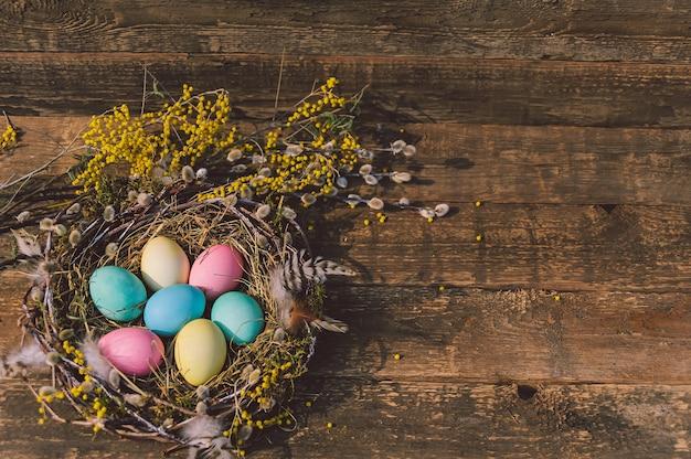 Ovos de páscoa coloridos no ninho. no contexto de uma placa de madeira.
