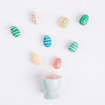 Ovos de páscoa coloridos perto de copo