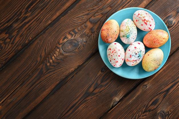 Ovos de páscoa coloridos pintados em uma placa azul em um fundo de madeira