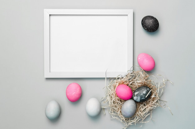 Ovos de páscoa coloridos pintados sobre fundo cinza e moldura para texto