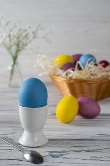 Ovos de páscoa coloridos tingidos em uma cesta com ovo azul em um copo