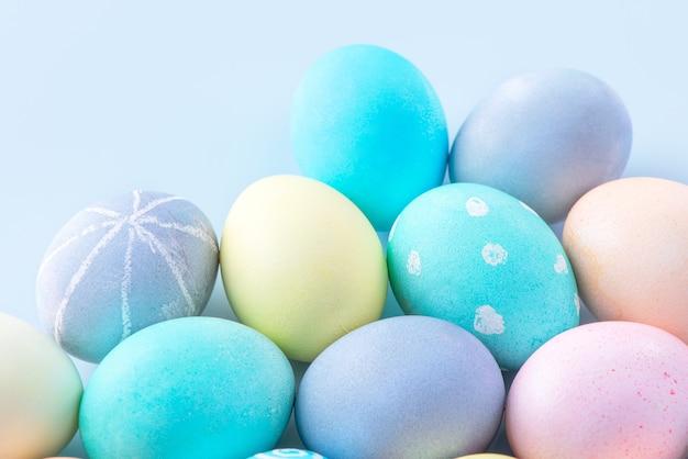 Ovos de páscoa coloridos tingidos por água colorida isolada em um fundo azul claro, conceito de design da atividade do feriado da páscoa, close-up, copie o espaço.