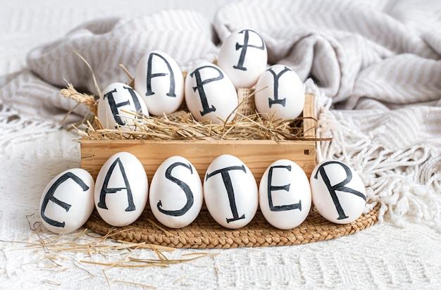 Ovos de páscoa com a inscrição feliz páscoa, decoração do feriado. natureza morta com clima aconchegante de páscoa.