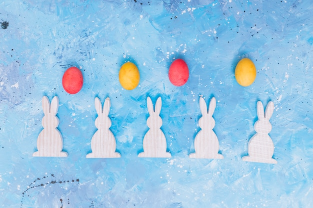 Ovos de páscoa com coelhos de madeira na mesa