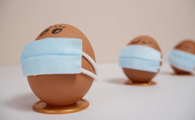 Ovos de páscoa com conceitos de proteção contra vírus. ovos de páscoa em uma máscara médica para decorar as férias da páscoa. em um fundo de pêssego com copyspace.
