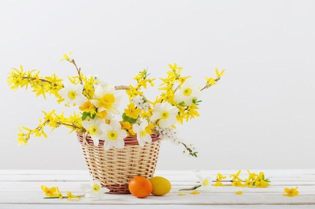 Ovos de páscoa com flores da primavera na mesa de madeira branca