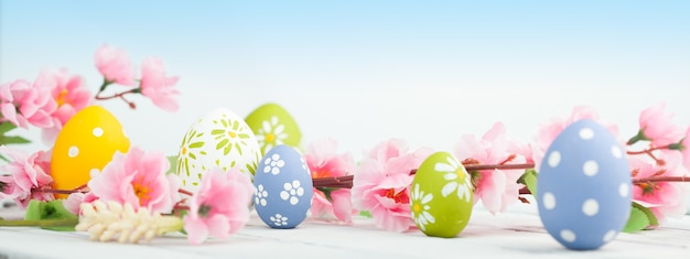 Ovos de páscoa com flores da primavera na mesa de madeira
