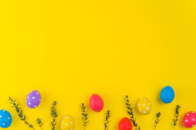 Ovos de páscoa com galhos de plantas na mesa amarela