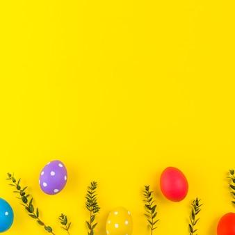 Ovos de páscoa com galhos de plantas na mesa