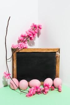 Ovos de páscoa com lousa e flores ramo na mesa