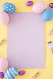 Ovos de páscoa com papel em branco na mesa amarela