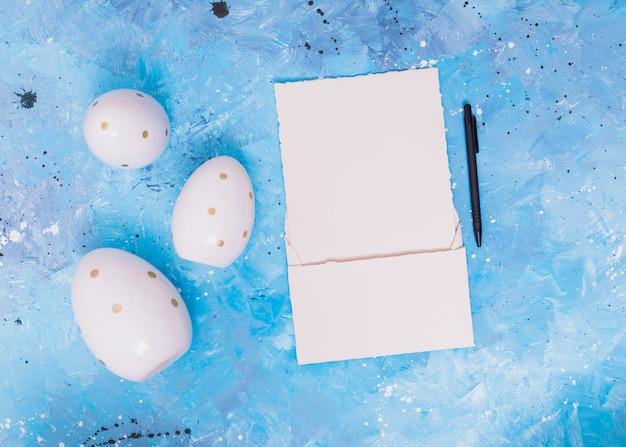 Ovos de páscoa com papel em branco na mesa