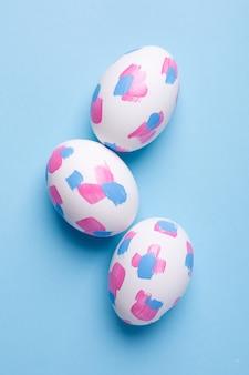 Ovos de páscoa com pinceladas de aquarela sobre uma superfície azul