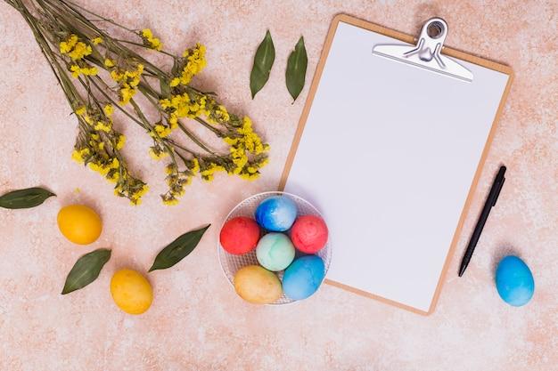 Ovos de páscoa com prancheta e flores