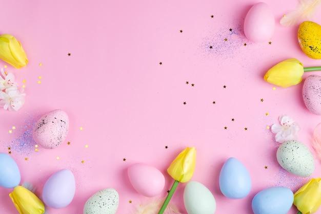 Ovos de páscoa com tulipas em fundo rosa estrelas