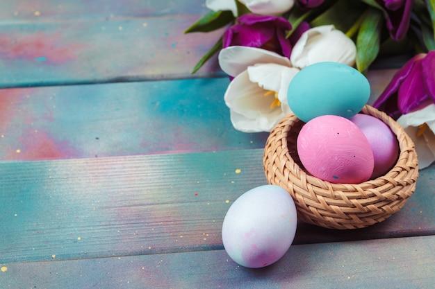 Ovos de páscoa com tulipas na mesa de madeira azul