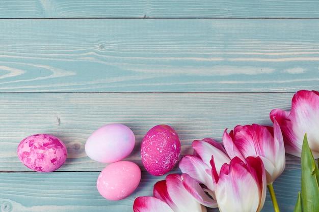 Ovos de páscoa com tulipas no fundo azul de madeira