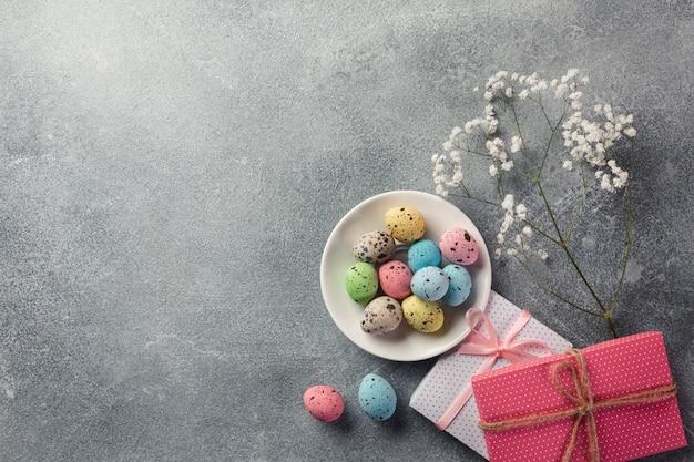 Ovos de páscoa com um presente na mesa de madeira. cartão de saudação vista superior com espaço para suas saudações.