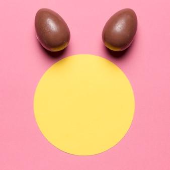 Ovos de páscoa como orelha de coelho sobre o quadro redondo de papel em branco contra o pano de fundo-de-rosa