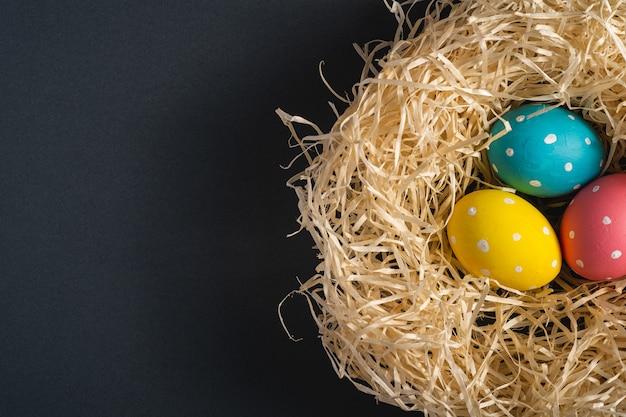 Ovos de páscoa de bolinhas coloridas no ninho de madeira no fundo liso preto cinza escuro, cartão, cópia espaço, vista superior