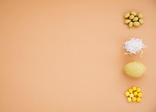 Ovos de páscoa de chocolate com pequenos doces na mesa