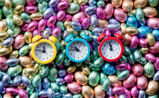Ovos de páscoa de chocolate de cor e três despertadores