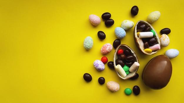 Ovos de páscoa de chocolate deliciosos, doces em fundo amarelo brilhante