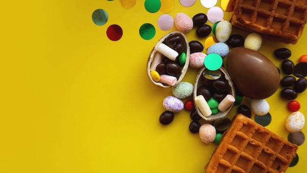 Ovos de páscoa de chocolate deliciosos, waffles e doces em fundo amarelo brilhante