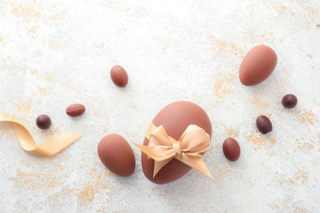 Ovos de páscoa de chocolate doce em superfície clara