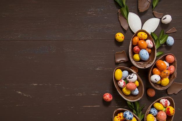 Ovos de páscoa de chocolate e coelho na mesa de madeira