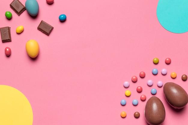 Ovos de páscoa de chocolate e doces de gema com espaço de cópia para escrever o texto no fundo rosa