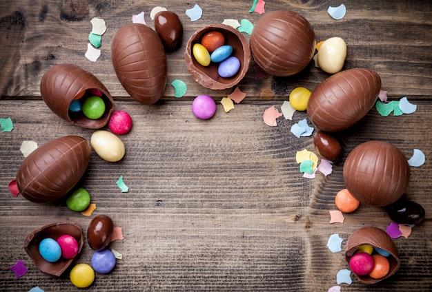Ovos de páscoa de chocolate e doces em fundo de madeira