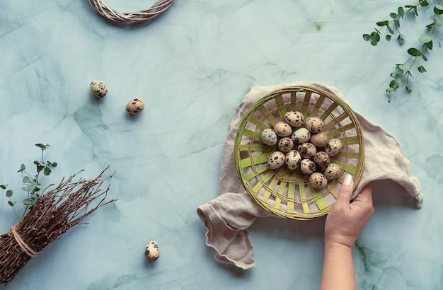 Ovos de páscoa de codorna, decorações de primavera e galhos de eucalipto. plano deitado em mármore verde claro.