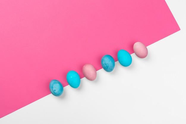 Ovos de páscoa de cor doce sobre fundo de papel brilhante