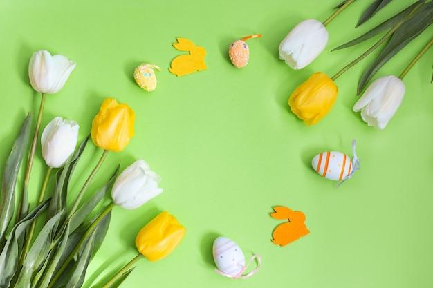 Ovos de páscoa de cor e coelho com tulipas brancas e amarelas sobre fundo verde.